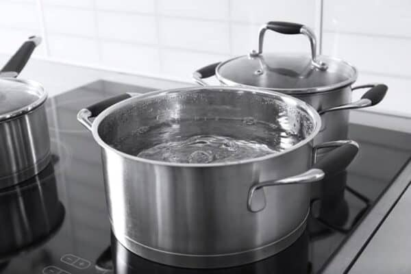 Metal pans with boiling water in kitchen
