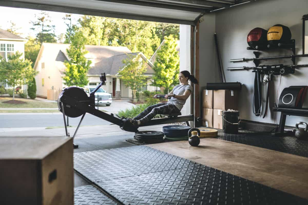 active woman exercising on a rowing machine in her royalty free image 1607437786.